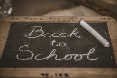 "Small chalkboard with ""Back to School"" written on it in cursive in white chalk."