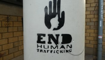 """Photo depicting a white pillar with black artwork of a hand with a human face stenciled inside it. Text reads """"END HUMAN TRAFFICKING."""""""