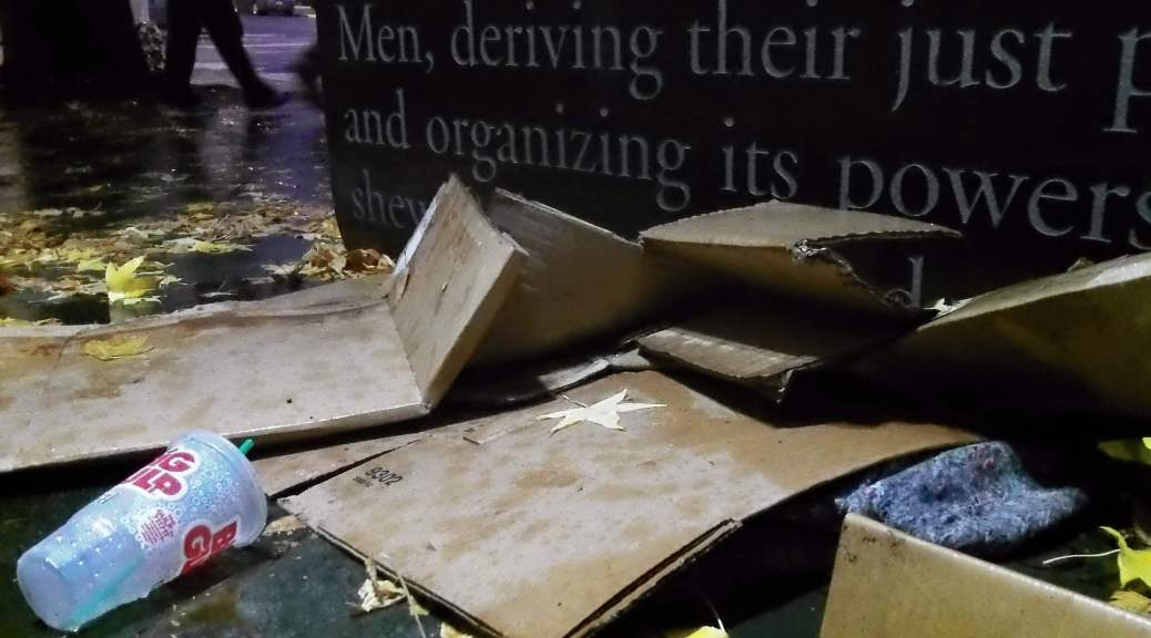 Photo of a homeless individual's belongings of food and cardboard in front of the steps of the U.S. District Court in Seattle.