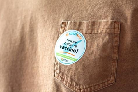 """Photo of a """"I got my COVID-19 vaccine"""" sticker on a brown shirt pocket."""