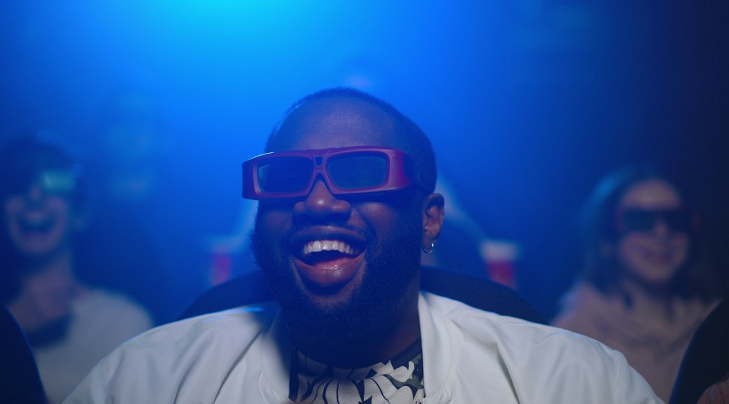 Photo of Black man wearing 3D glasses, laughing at movie