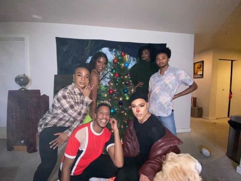 Photo of the Royal House of Noir gathered around a Christmas tree and smiling at the camera.
