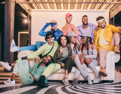 A diverse and joyful group of youthful queer folks pose on and behind a couch wearing pastel-colored clothing.