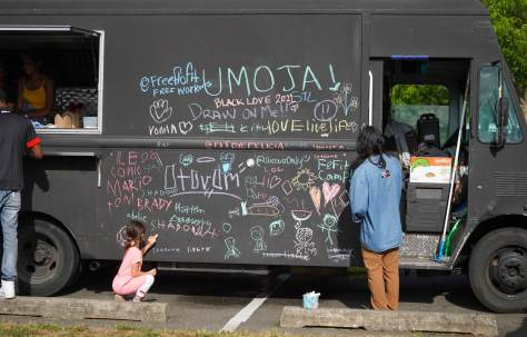 Festival goers writing messages in color chalk on the blackboard-painted food truck.