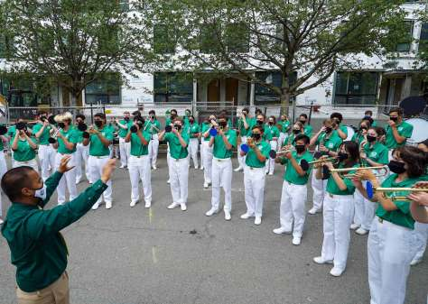 Photo of the Seattle All-City Marching Band in their bright-green uniform shirts with bright-white trousers gathered in a semi-circle around a conductor.