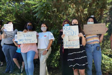 Photo of female-presenting individuals standing in a line holding protest signs.