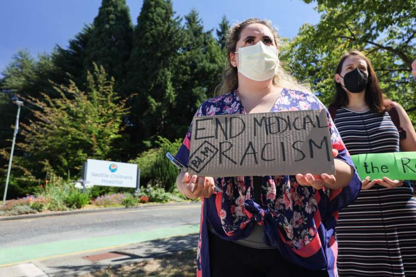 """Photo of female-presenting individuals standing at the entrance of Seattle Children's Hospital's parking lot/entrance carrying protest signs; the protestor in the foreground's sign reads, """"END MEDICAL RACISM BLM."""""""