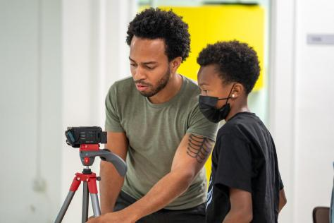 Instructor Obadiah Freeman helps film student Terry Hill, 11, position the camera during the five-day Reel Youth Film Camp August 16—20 at the Rainier Arts Center. (photo: Susan Fried)
