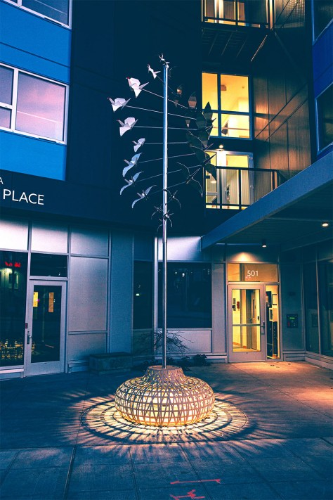 """Photo depicting Chinn's artwork """"Returning Home,"""" a sculpture with origami-style cranes attached to a pole that move in the wind. A light at the base of the piece shines on the plaza."""