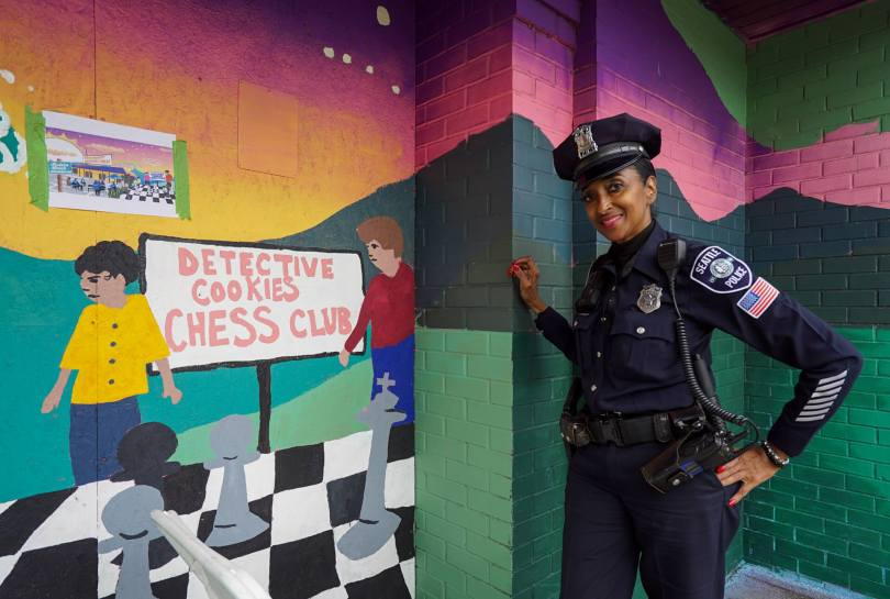 """Photo depicting Seattle Police Detective Denise """"Cookie"""" Bouldin poses by a part of a new mural located across the street from Detective Cookie Chess Park."""