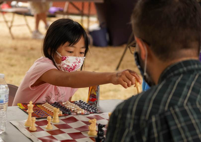 Photo depicting a female-presenting youth in a pink shirt with a pink-floral surgical face mask moving a chess piece.