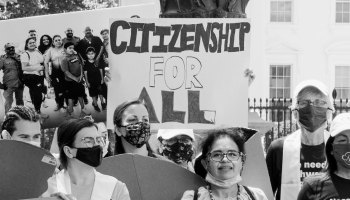 """Black-and-white photo depicting a DACA rally in Lafayette Square with masked protestors holding signs that read """"Citizenship for ALL."""""""