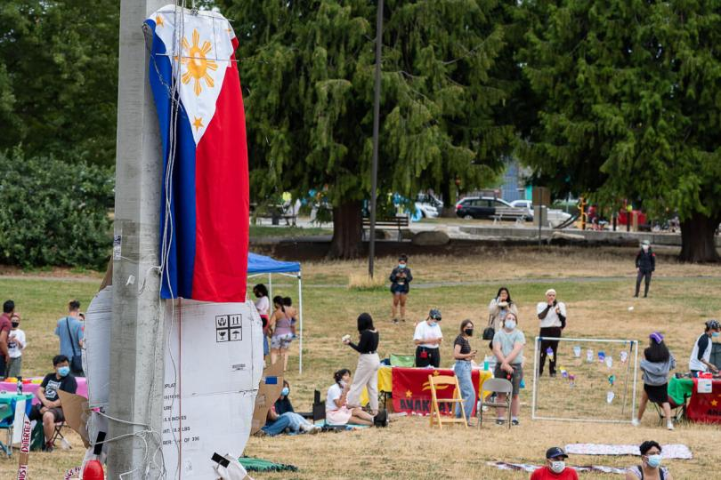 The flag of the Philippines hangs over Othello Park as the crowd listens to a speaker.