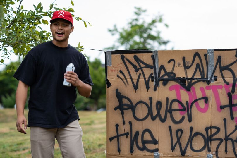 Local Filipino American rapper and artist Theomatic stands by a graffiti piece that he worked on during the event.