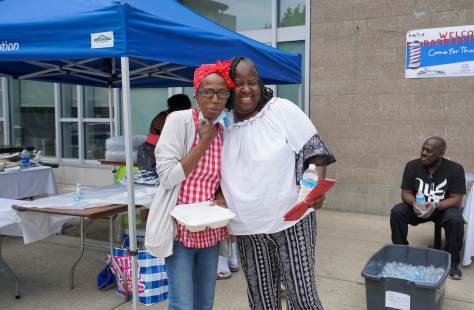"""Friends Yvette Dinish and F.A.S.T Co-Director Cathie Wilmore greet each other at the annual """"Barbershop Cut, Chat, Chew, and Play"""" event"""