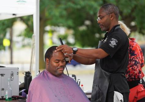 Kenny gets his hair cut by Aaron Lucas, an SPD police officer and a barber at Brooks Family Barbershop