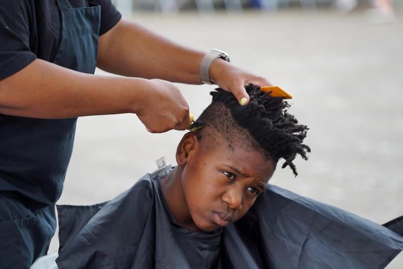 Adetokunbo Amoda, 10, has his hair cut by Jocelyn Mayhle from Frank's Barbershop