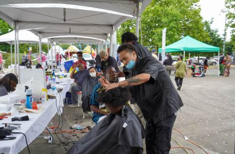 Photo of barbers and clients in barber chairs receiving haircuts at the Barbershop Cut, Chat, Chew, and Play event in Rainier Beach.