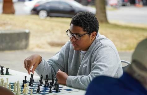 Chukundi Salisbury Jr., 15, plays chess in the Detective Cookie Chess Club tent