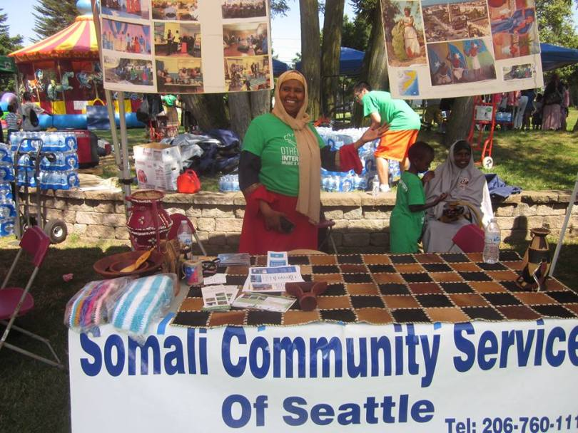 """Photo depicting a female-presenting individual at an outdoor with a sign draped in front of the table that reads """"Somali Community Services of Seattle."""""""