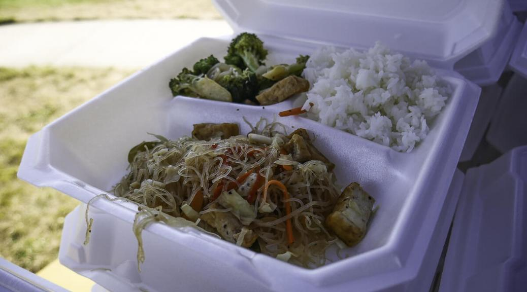 Photo of a Styrofoam container filled with pancit, rice, and stir-fried veggies.