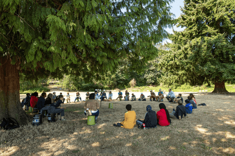 Photo depicting individuals sitting in a circle, some on buckets, in a grassy park under a tree.