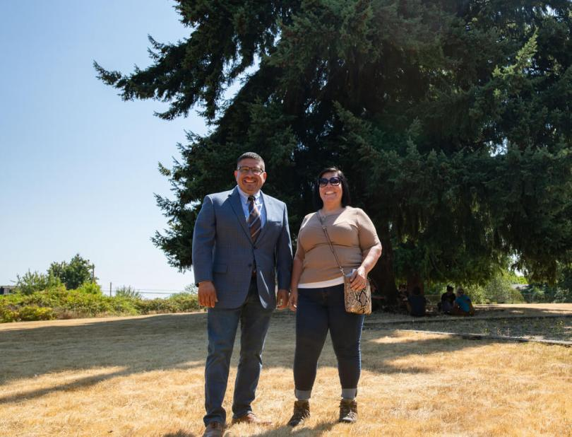Photo of the mayor of Burien standing next to another individual in Hilltop Park, a large evergreen tree in the background.