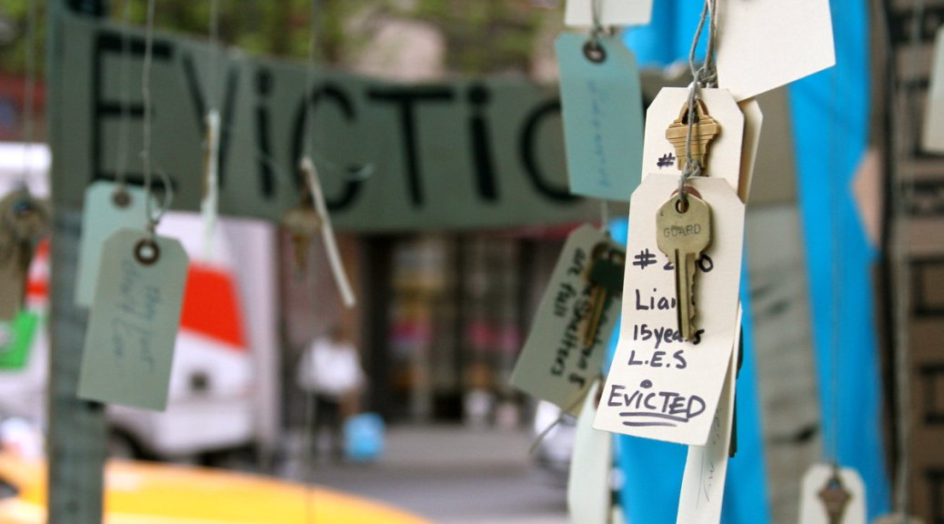 """Photo depicting an exhibit with keys hanging with tags that have information about those evicted. In the blurred background a large banner reads """"Eviction"""" and in the foreground one visible key tag reads """"Liang 15 years L.E.S. EVICTED."""""""