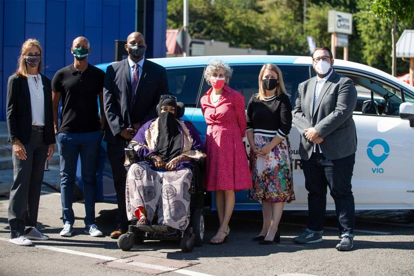 Photo of elected officials and community leaders wearing surgical masks in front of a Via to Transit vehicle.