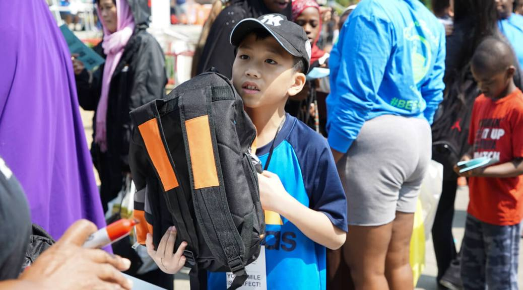 Photo depicting a male-presenting youth, wearing a blue Adidas t-shirt and black baseball cap, picking up a backpack from a volunteer holding a red marker. Behind the youth are groups of individuals picking up various school supplies.