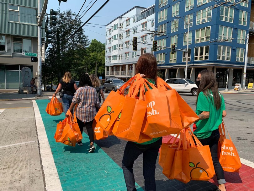 """Photo depicting Amazon Fresh workers carrying a bunch of bright-orange Amazon Fresh reusable shopping bags with the words """"Shop fresh"""" printed in white across the bags while crossing 23rd Avenue South."""