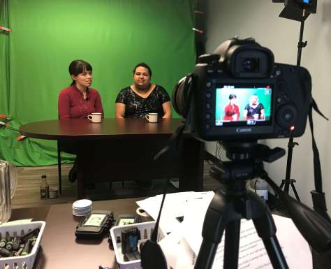 Photo depicting filming of an interview session for Rooted in Rights with two female-presenting individuals seated at a table in front of a green screen, the camera in the foreground.
