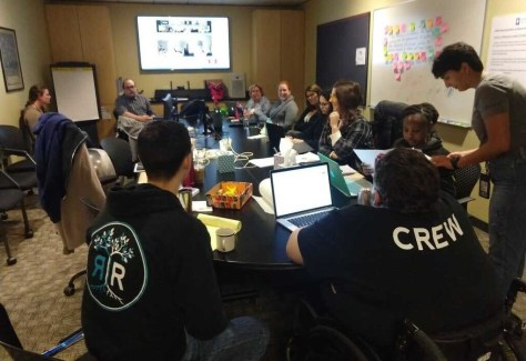 Photo depicting a newsroom meeting with many crewmembers seated around a conference room table.