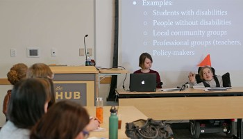 Photo depicting a panel discussion on the topic of disability with two presenters seated in front of a projector screen with a slideshow display behind them.