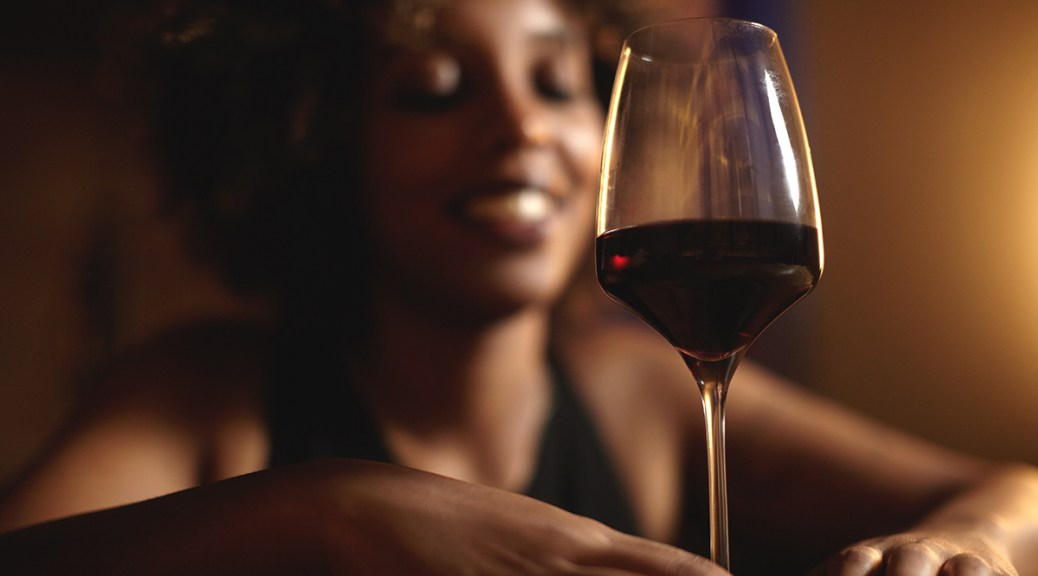 Photo depicting a Black, female-presenting individual holding a glass of red wine. The woman in the background is blurred.