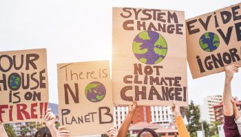 Photo depicting Group of demonstrators on road, young people from different culture and race fight for climate change - Global warming and enviroment concept - Focus on banners