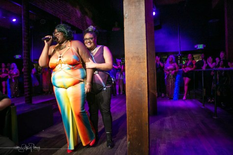 Photo depicting Mx. Pucks A'Plenty and Rebecca Mm Davis inside a blue-lit bar speaking into a microphone.