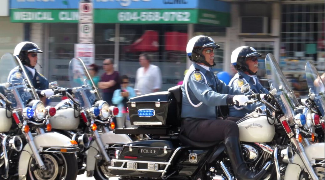 Photo depicting Seattle police officers on police motorcycles riding by on a city street.