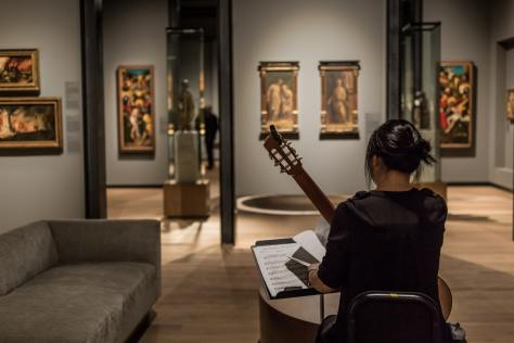 Photo depicting a female-presenting guitarist with her back to the camera in an art museum next to a gray couch. The guitarist is flipping through sheet music while holding an acoustic guitar.