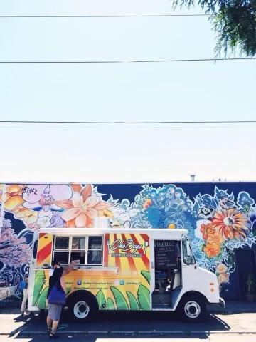 Photo depicting the red-yellow-and-green CheBogz food truck parked in front of a blue-floral mural.
