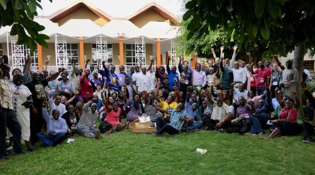 Photo depicting a large group of individuals gathered on a lawn with fists raised at a summit in Senegal.