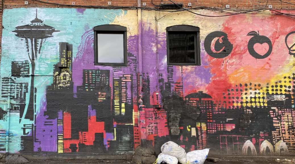 Photo depicting a colorful street mural of the Seattle skyline on the side of a brick building.