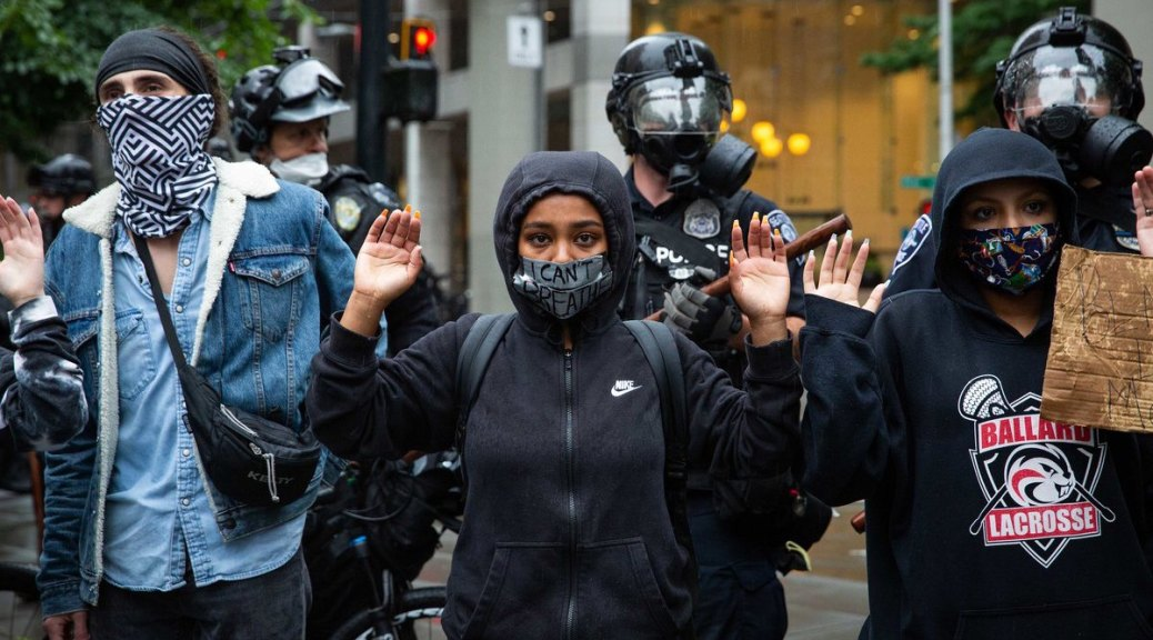"""At a BLM protest, a Black person in a black hoodie stands center frame with hands raised, their mouth covered in duct tape with the words """"I can't breathe"""" written on it. Other protesters flank this person and police in riot gear can be seen in the background."""