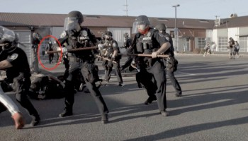 """Screen capture from video by Chris Rojas of the police action against protesters at SPOG on Labor Day 2020. Subject """"Tan Gloves"""" is circled."""
