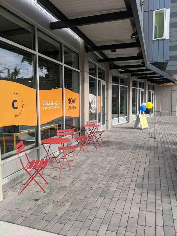 """Photo depicting a close-up view of the retail level of the Colina Apartments building with an orange-waved window sign that reads """"Now Leasing."""" Red folding outdoor chairs and stables sit outside the entrance to the space."""