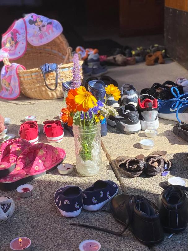 Photo depicting a memorial with babies' and children's shoes surrounded by flowers and tealight candles.