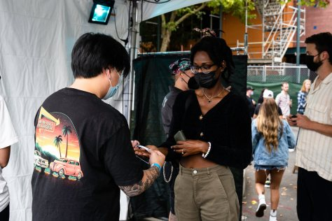 Photo depicting a female-presenting individual with a black surgical face mask viewing a vaccination card of another individual inside an event tent.