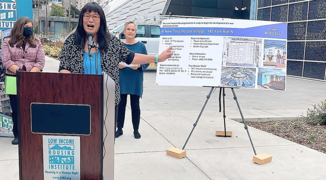 """Photo depicting Sharon Lee standing at a podium and microphone speaking and gesturing to a land-use poster with text that reads """"A New Tiny House Village."""""""