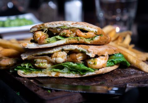 Photo depicting a sandwich made with cuban bread, prawns, and bright-green lettuce and sauce.