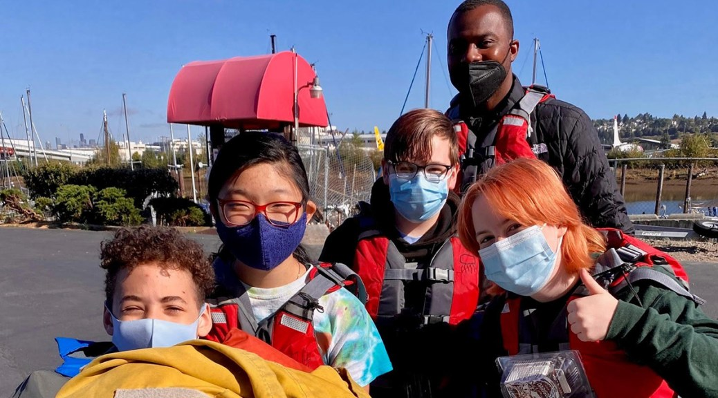 Photo depicting youth wearing surgical face masks and life jackets smiling by a waterway. Their instructor stands behind him.